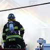 A Danvers firefighter sprays a steady stream of water up at  8 Sylvan Street in Danvers on Friday afternoon after a 3-alarm fire broke out. DAVID LE/Staff photo. 6/20/14