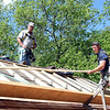David Johnston Jr., right, lays a piece of wood across the roof of the Nathaniel Felton Sr. House in Peabody, under the watchful eye of his father, David Johnston Sr. DAVID LE/Staff photo. 6/19/14.