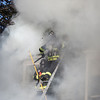 A Danvers firefighter while engulfed in a large cloud of smoke takes out a third floor window to try and let the fire escape during a 3-alarm fire that broke out at 8 Sylvan Street in Danvers on Friday afternoon. DAVID LE/Staff photo. 6/20/14