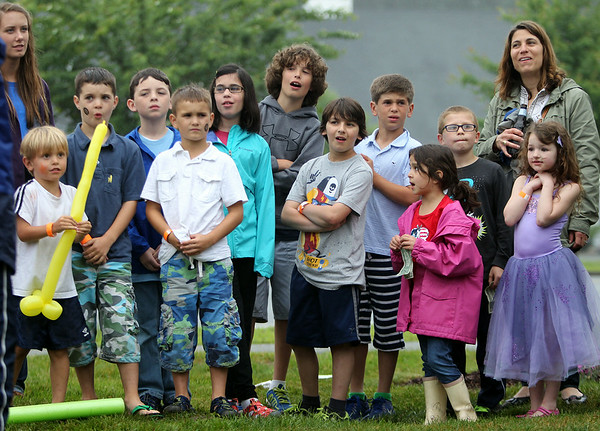 Excited onlookers wait in anticipation as people throw baseballs at the dunk tank trying to dunk Fire Chief Kirby Brand during the 6th annual block party held at the Hamilton-Wenham Community House on Friday afternoon. DAVID LE/Staff photo. 4/13/14.