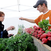 KEN YUSZKUS/Staff photo. Marie Brescia of Salem buys greens from the owner of Grant Family Farm in Essex, Chris Grant, on the opening day of the farmers market, now in its 6th season.    6/12/14.