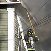 A Danvers firefighter uses a sharp spear to try and poke a hole in a corner of the roof of 8 Sylvan Street in Danvers on Friday afternoon after a 3-alarm fire broke out. DAVID LE/Staff photo. 6/20/14