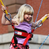 Five-year-old Kennedy Sharar, of Andover, flashes a wide smile while bouncing up and down on a bungee jump at Oldies Night in downtown Danvers on Wednesday evening. DAVID LE/Staff photo. 6/25/14.