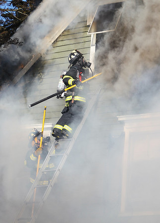 Smoke streams out of a third floor window after a Danvers firefighter poked a hole through the glass, allowing the smoke and fire to escape. A 3-alarm fire broke out at 8 Holten Street in Danvers on Friday afternoon. DAVID LE/Staff photo. 6/20/14