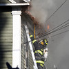 A Danvers firefighter is sprayed with burning debris after ripping down a chunk of the rooftop of 8 Sylvan Street while trying to cut a hole for the fire to escape. A 3-alarm fire broke out at 8 Sylvan Street in Danvers on Friday afternoon. DAVID LE/Staff photo. 6/20/14