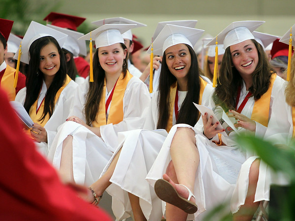 "From left: Masconomet Regional High School graduates Alex Mendelsohn, Katherine Lemiesz, Julianna Kostas, and Madison Kelly smile as they listen to Class President Rebecca Stone's speech called ""Moving Up & Moving On"" during graduation on Friday evening. DAVID LE/Staff photo. 6/6/14."