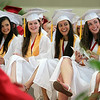 """From left: Masconomet Regional High School graduates Alex Mendelsohn, Katherine Lemiesz, Julianna Kostas, and Madison Kelly smile as they listen to Class President Rebecca Stone's speech called """"Moving Up & Moving On"""" during graduation on Friday evening. DAVID LE/Staff photo. 6/6/14."""
