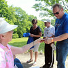 Julie O'Neill, of Medford, hands a ticket to Michael Peebles, also of Medford, after he answered a question correctly during the It's My Heart Walk at Endicott Park in Danvers on Sunday morning. DAVID LE/Staff photo. 6/29/14.
