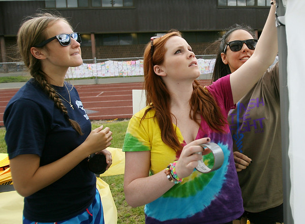 From left, Peabody High School graduates Michelle Cali, Carolyn Deroo, and Amanda Alperen tape up black and yellow streamer decorations to their Relay for Life tent on Friday afternoon. DAVID LE/Staff photo. 6/6/14.