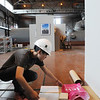 KEN YUSZKUS/Staff photo. Student Joyce Tat works on installing the Montserrat College of Art student's art show inside the Salem Power Plant.   6/9/14.