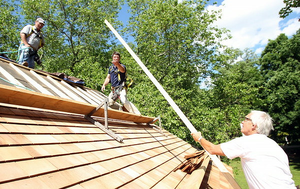 Tom Zellen, right, hands a plank of wood up to David Johnston Jr., center, while repairing the roof the the Nathaniel Felton Sr. House in Peabody on Thursday afternoon. DAVID LE/Staff photo. 6/19/14.