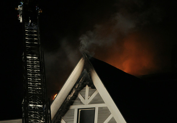 The fire burns and illuminates a thick smoke leaking from the roof of the Eastern Yacht Club. A 3-alarm fire broke out at the Eastern Yacht Club in Marblehead early Friday morning. DAVID LE/Staff photo. 6/12/14