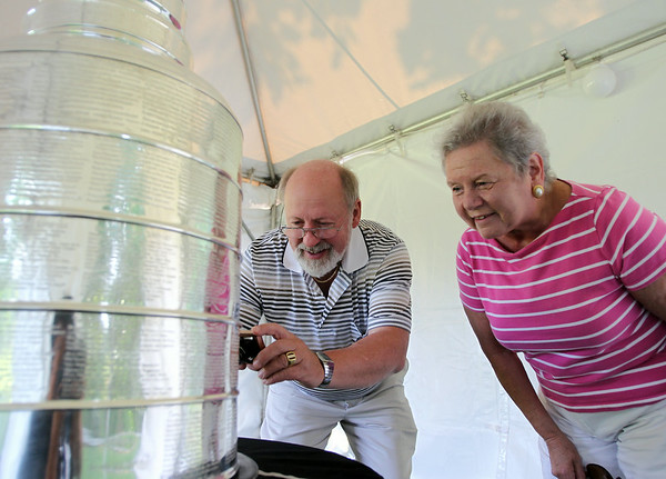 Jan and Ken Lisiak, of Middleton, take a photo of the Stanley Cup at the house of Mark Yanetti in Topsfield on Sunday morning. Yanetti, the Director of Amateur Scouting for the Los Angeles Kings won the Cup for the second time in three years. DAVID LE/Staff photo. 6/29/14.