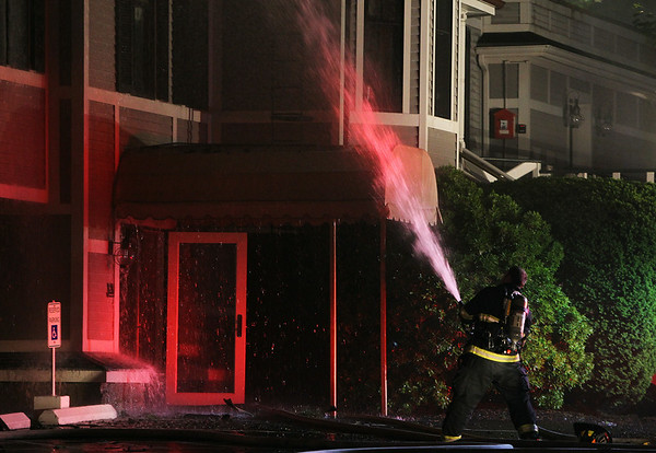 A firefighter sprays water towards the top of the Eastern Yacht Club after a 3-alarm fire broke out early Friday morning. DAVID LE/Staff photo. 6/13/14