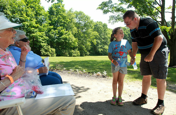 Jada Coburn, 9, of Greene, ME, talks with her father Christopher, while answering a question during the Keep the Beat It's My Heart Walk at Endicott Park in Danvers on Sunday morning. DAVID LE/Staff photo. 6/29/14.