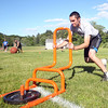 Swampscott senior Charlie Arena pushes a weighted sled across the finish line during the Lineman Challenge at Masconomet Regional High School, a competition for local high school offensive and defensive linemen and run by Masco head football coach Jim Pugh. DAVID LE/Staff photo. 6/20/14.