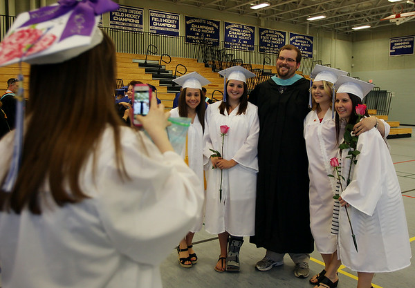 Danvers High School graduate Christina Prendergast, left, takes of photos of her classmates Krystin Belthoff, Nicole Harrison, Math teacher Tofer Carlson, Kalyn Flint, and Rachael Barrows prior to the start of graduation on Saturday afternoon. DAVID LE/Staff photo. 6/7/14.