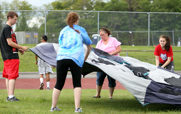 From left, Will Scully, Brianna Swan, Melissa Swan, and Alex Schwartz, all of Salem, set up their tent at the Peabody High School Relay for Life on Friday afternoon. Melissa Swan walked last year as a survivor and vowed to return for the whole event this year. DAVID LE/Staff photo. 6/6/14.