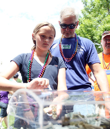 Ten-year-old Kyra Jagolta, of Salem, tries a possible key for the Eastern Bank Treasure Chest, as her father Rich looks on at the annual Gay Pride Parade festivities at Salem Common on Saturday afternoon. DAVID LE/Staff photo. 6/21/14.