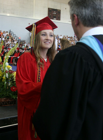 Marblehead High School graduate Lily Roberts shakes hands with Principal Layne Millington after receiving her diploma on Sunday afternoon. DAVID LE/Staff photo. 6/8/14.