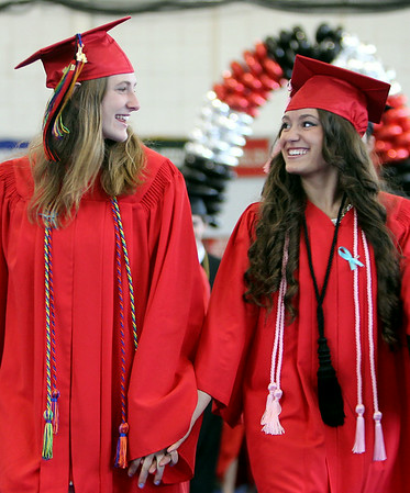 Marblehead High School senior class president Lily Cummings, left, and senior class vice-president Alea Moscone, right, flash each other a big smile as they lead the 2014 graduating class in hand-in-hand. DAVID LE/Staff photo. 6/8/14.
