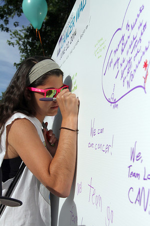 MARIA UMINSKI/SALEM NEWS Julia Carter of Methuen leaves a message on the the North Shore Cancer Walk wall before starting the 6.2 mile walk with Team Landry on Sunday June 22, 2014.