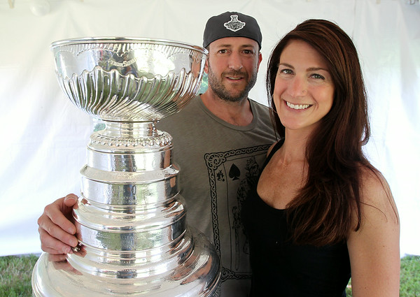 Mark Yanetti and his wife Kristen stand with the Stanley Cup at a Cup viewing party held at the Yanetti household in Topsfield on Sunday morning. Yanetti, the Director of Amateur Scouting for the Los Angeles Kings won the Cup for the second time in three years. DAVID LE/Staff photo. 6/29/14.