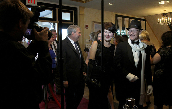 MARIA UMINSKI/SALEM NEWS Dr. Peter Hjorth and his wife Mikki Hjorth pose for the paparazzi photographers as they walk the red carpet on their way into the Danvers Family Festival kick-off event, Horray for Hollywood at the Danversport Yacht Club on Friday night.