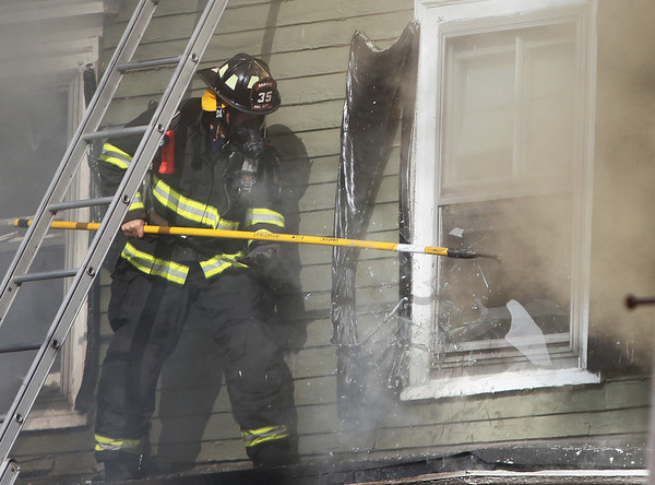 A Danvers firefighter uses a long pole to shatter the glass of a second story window, trying to allow the fire which started in a home at 8 Sylvan Street, to escape. A 3-alarm fire broke out at 8 Sylvan Street in Danvers on Friday afternoon. DAVID LE/Staff photo. 6/20/14