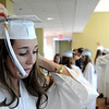 KEN YUSZKUS/Staff photo. Graduates Sam Charette dons her motarboard before the begining of the Hamilton Wenham graduation at Gordon College Chapel.   6/1/14.