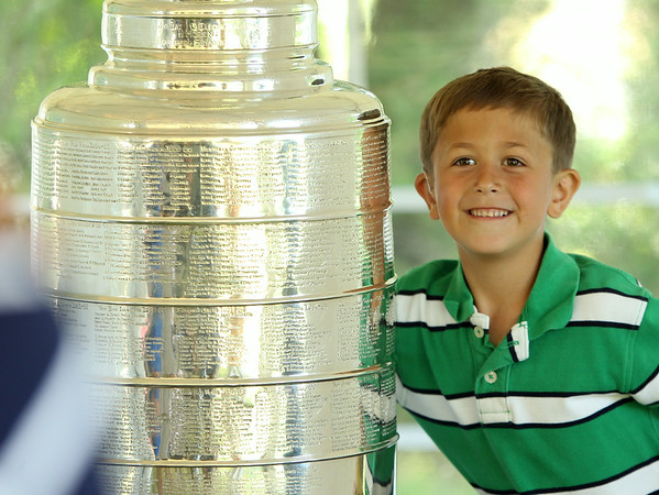 Joseph DeFilippo, of Reading, poses for a photo with the Stanley Cup at the house of Mark Yanetti, in Topsfield on Sunday morning. Yanetti, the Director of Amateur Scouting for the Los Angeles Kings won the Cup for the second time in three years. DAVID LE/Staff photo. 6/29/14.