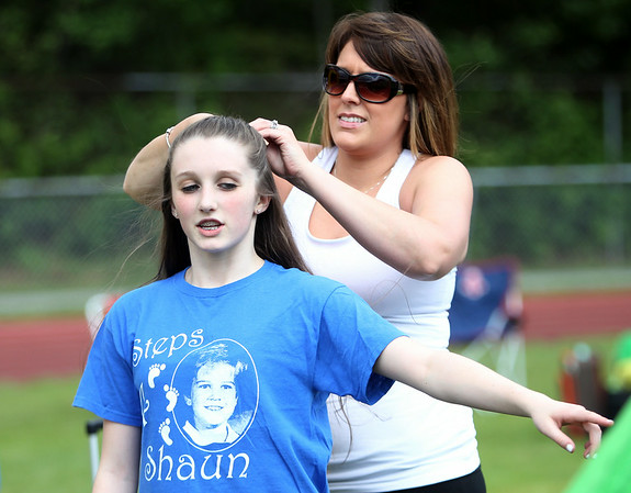 Brianna Sano, left, of Salem, has her hair braided by Melissa Field, also of Salem, at the Peabody High School Relay for Life. DAVID LE/Staff photo. 6/6/14.