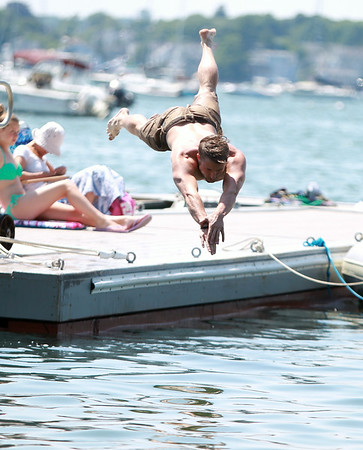 Marblehead native Kagan Sinclair takes a headfirst dive into Salem Harbor to cool off on a hot Monday afternoon. DAVID LE/Staff photo. 6/30/14.