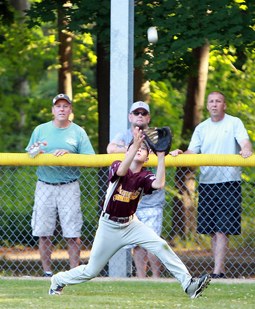 Danvers National right fielder Liam McKenna hauls in a deep fly ball against Hamilton-Wenham on Monday evening. DAVID LE/Staff photo. 6/30/14.
