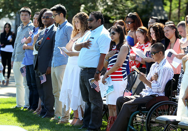 Newly sworn in United States citizens place their hands over their hearts during the Pledge of Allegiance during a Naturalization ceremony on the back lawn of the House of Seven Gables in Salem on Friday afternoon. DAVID LE/Staff photo. 6/27/14.