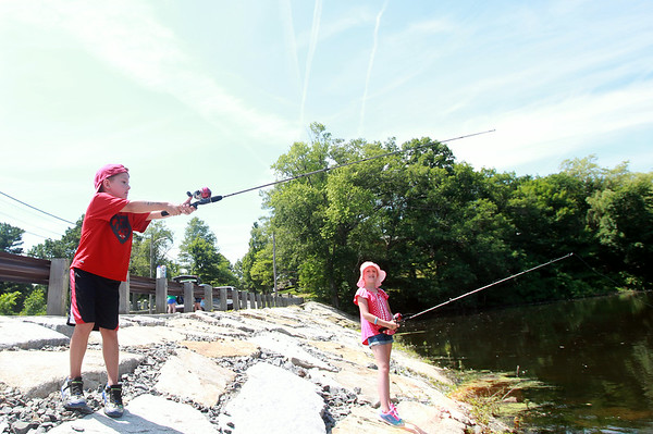 Owen Hazelbaker, 5, casts his fishing line under the watchful eye of his sister Lily, 8, during the fishing derby at Mill Pond in Danvers on Sunday morning. DAVID LE/Staff photo. 6/29/14.
