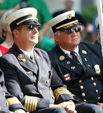 Chief Paul Cotter, of the Beverly Fire Department, left, and Steven Pasdon, of the Peabody Fire Department, listen to remarks by Salem Mayor Kim Driscoll during a commemoration ceremony for the Great Salem Fire of 1914 on Wednesday afternoon. DAVID LE/Staff photo. 6/25/14.