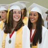 Masco graduates Madison Kelly, left, and Julianna Kostas, right, share a laugh as they wait for their classmates to file in at the start of graduation on Friday evening. DAVID LE/Staff photo. 6/6/14.
