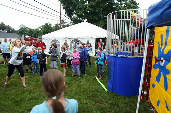 Hamilton-Wenham freshman Brynne O'Connor, left, throws a baseball at the dunk tank during the 6th annual block party held at the Hamilton-Wenham Community House on Friday afternoon. DAVID LE/Staff photo. 4/13/14.