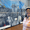 KEN YUSZKUS/Staff photo. Beth Tobin stands near a large mural that portrays her at work in the lower left of the painting. The mural is part of the Montserrat College of Art student's art show inside the Salem Power Plant.   6/9/14.