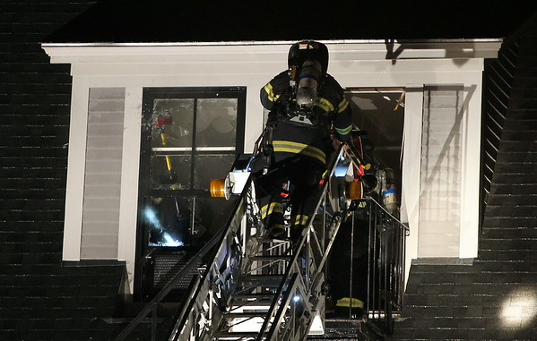 Firefighters climb up to the upper levels of the Eastern Yacht Club and knock out windows and doors, trying to ventilate the roof and allow any remaining fire to escape. A 3-alarm fire broke out at the Eastern Yacht Club in Marblehead early Friday morning. DAVID LE/Staff photo. 6/13/14