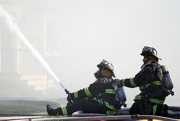 Two Danvers firefighters spray water upwards at 8 Sylvan Street after a 3-alarm fire broke out on Friday afternoon. DAVID LE/Staff photo. 6/20/14
