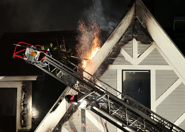 Sparks fly from the roof of the Eastern Yacht Club in Marblehead as a firefighter saws through the shingles to cut an opening to let the fire escape. A 3-alarm fire broke out at the Eastern Yacht Club in Marblehead early Friday morning. DAVID LE/Staff photo. 6/13/14