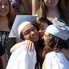 "Danvers High School senior chorus members Nicole Camarro, left, and Alex Skameas, right, get a big hug from sophomore Cece DiGregorio, center, after they sang ""Home"" for the last time together during graduation on Saturday afternoon. DAVID LE/Staff photo. 6/7/14."