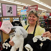 "Polly Hamilton, Assistant Manager at Petco, holds up a few different costumes that can be purchased for a free ""Dog Wedding Day"" on June 28th. The store will be selling wedding dresses and tuxes for the participating dogs. DAVID LE/Staff photo. 6/20/14."