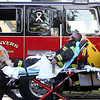 An injured Beverly firefighter is taken away on a stretcher by two EMT's during a 3-alarm fire broke out at 8 Sylvan Street in Danvers on Friday afternoon. DAVID LE/Staff photo. 6/20/14