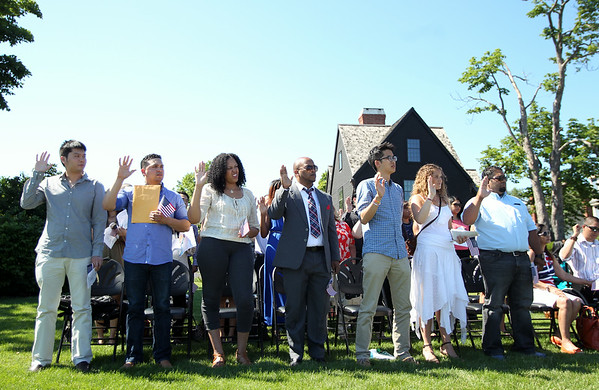 New United States citizens raise their right hand and recite an Oath of Allegiance as read by Tracy McLaughlin, Deputy Clerk from the US District Court, during a Naturalization ceremony on the back lawn of the House of Seven Gables in Salem on Friday afternoon. DAVID LE/Staff photo. 6/27/14.