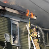 A firefighter uses a spear to try and remove a chunk of the roof of 8 Sylvan Street after a 3-alarm fire broke out on Friday afternoon. DAVID LE/Staff photo. 6/20/14
