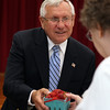 Former Peabody Mayor Michael Bonfanti smiles while handing out strawberry baskets during the first of a new weekly farmers market held by the Peabody Council on Aging and Lahey Health at the Torigian Center on Friday afternoon. DAVID LE/Staff photo. 6/20/14.