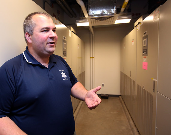 KEN YUSZKUS/Staff photo.  Deputy director of the Essex County Regional Communications Center in Middleton Christopher Ryan talks about the batteries contained in the room for flawless switch over to emergency power if needed.   6/01/15